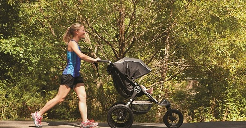 A woman jogs in the park while pushing a stroller.